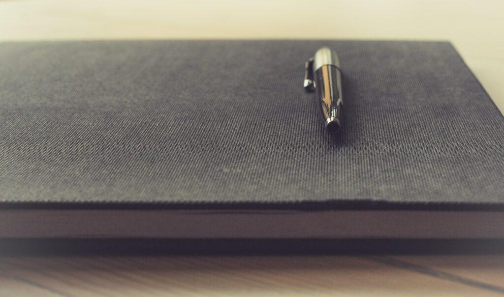 bog med kuglepen ovenpå